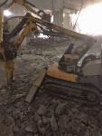Puolustusvoimissa hajoittamassa taloa robolla ja kaivurilla